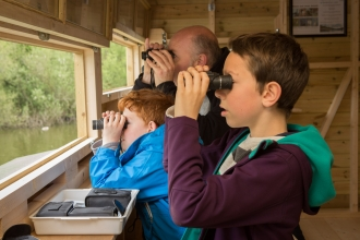 Family birdwatching in hide