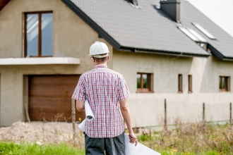 Man with hard hat and architect drawings walking towards half built house