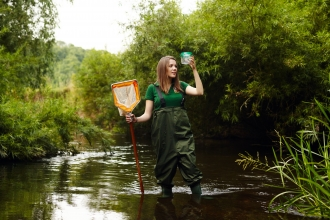 Girl standing in river in waders with net and jar