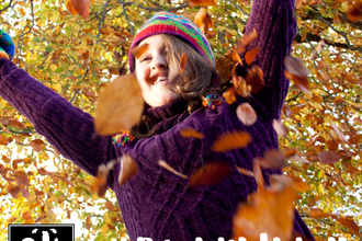 Girl throwing autumn leaves into the air