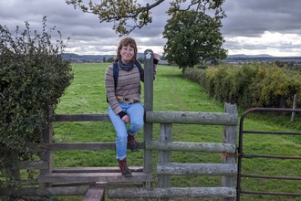 Woman sitting on a stile with green field behind with hedgerows each side