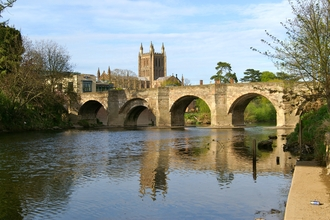 View of wide river flowing under 4 arches of a stone bridge with cathedral tower behind