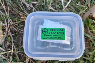 Plastic box with green sticker on lid on the grass