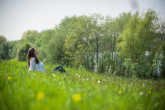 Woman in white top say leaning back in meadow with trees in background