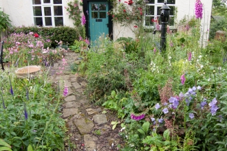 Cottage garden with path leading to blue door