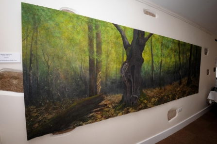 Painting of a woodland hung in a gallery