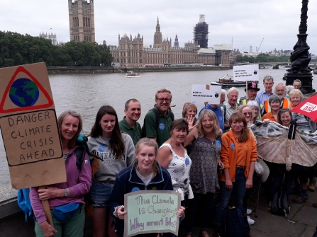 Group with placards with the Thames and Houses of Parliament in the background