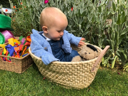 A very young child sat in a basket with a teddy in a garden